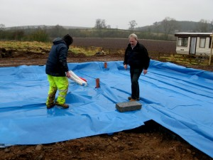 Stan and Seely position the damp proof membrane